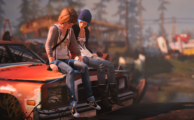 Two femme looking people sitting on a car bonnet in a junkyard.